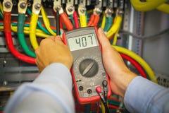 Multimètre dans des mains d'électricien sur le fond des cables électriques en gros plan Tension de mesure par l'instrument photos libres de droits