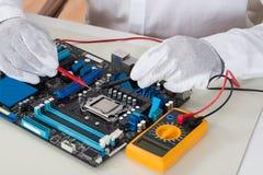 Multimètre de Person Hands Checking Motherboard With photo libre de droits