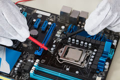 Multimètre de Person Hands Checking Motherboard With photo stock