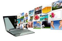 Multimedia che effluiscono dallo schermo del computer portatile Fotografie Stock Libere da Diritti