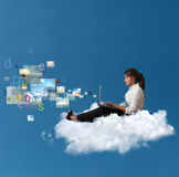 Multimedia on notebook. Concept of multimedia with a businesswoman over a cloud with a laptop stock photo