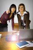 Multimedia Presentation. Two women are standing at the table. There's working multimedia projector on it and laptop. One woman's pointing on the screen royalty free stock photography