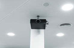 Multimedia projector on the ceiling. Multimedia projector hanging on the ceiling of modern conference room. Monochrome indoors picture Royalty Free Stock Images