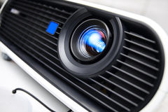 Multimedia projector closeup. Face of white multimedia projector. Close-up lens. Nobody. Tilt view with shallow DOF stock photography