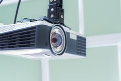 Multimedia projector hanging on the ceiling of modern conference room. Monochrome indoors picture. Royalty Free Stock Photography
