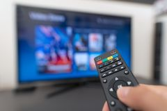 Multimedia streaming concept. Hand holding remote control. Video on demand stock images