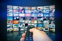 Multimedia video wall television broadcast. Hand holding remote control royalty free stock photos