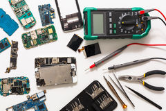 Multimeter and broken mobile electronics at repair shop Royalty Free Stock Photo