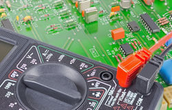 Multimeter closeup and circuit board Royalty Free Stock Photo