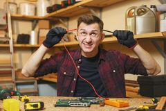Handsome smiling young man working in carpentry workshop at wooden table place with piece of wood. Multimeter for electrician. Crazy aggressive batty mad fun Stock Image