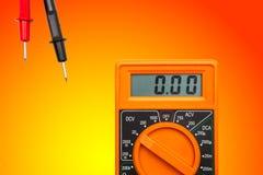 Multimeter on gradient yellow orange background. Orange color electric Multimeter device on gradient yellow orange background royalty free stock photo