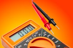 Multimeter on gradient yellow orange background. Orange color electric Multer device on gradient yellow orange background stock image
