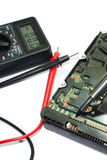 Multimeter and hard disc. Repairing hard disc on the white background. Measuring with multimeter stock photo
