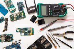 Multimeter i łamane mobilne elektronika przy remontowym sklepem zdjęcia stock