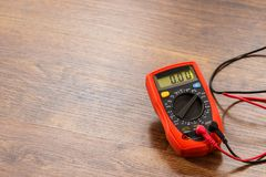 Multimeter for measurement of voltage. Multimeter measuring device electric tool for measurement of voltage lying on wooden floor background stock photo