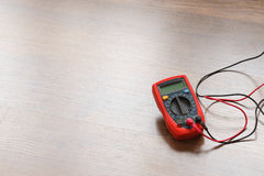 Multimeter for measurement of voltage. Multimeter measuring device electric tool for measurement of voltage lying on wooden floor background royalty free stock photography