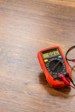 Multimeter for measurement of voltage. Multimeter measuring device electric tool for measurement of voltage lying on wooden floor background royalty free stock image