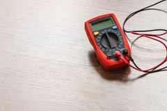 Multimeter for measurement of voltage. Multimeter measuring device electric tool for measurement of voltage lying on wooden floor background royalty free stock photos