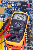 Multimeter and motherboard Royalty Free Stock Photo