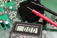 Multimeter on PCB plate. Royalty Free Stock Image