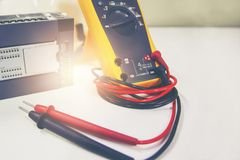 Multimeter with PLC placed on white table. Multimeter yellow color with PLC placed on white table Stock Images