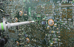 Multimeter probes examining a circuit board. Multimeter probes examining a PCB circuit board Stock Image