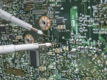 Multimeter probes examining a circuit board. Multimeter probes examining a PCB circuit board Stock Photo