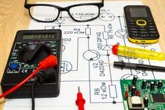Multimeter probes examining a computer circuit board and circuit. Multimeter probes examining the computer Board on the background of the circuit stock photos