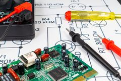 Multimeter probes examining a computer circuit board. Multimeter probes examining the computer Board on the background of the circuit stock image