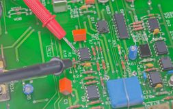 Multimeter probes examining a computer circuit board. Electric measuring a printed circuit board Stock Image