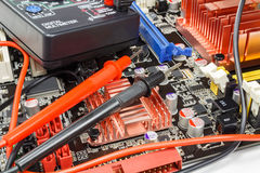 Multimeter probes on the motherboard surface closeup Stock Image