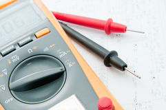 Multimeter on the white circuit paper. Multimeter lay down the white circuit paper ,preparing for check Electronic Value Stock Photos