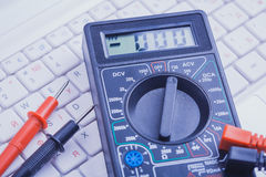 Multimeter on the white laptop. close-up Stock Image