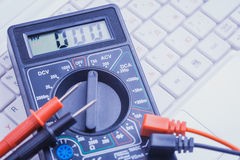 Multimeter on the white laptop. close-up Royalty Free Stock Photography