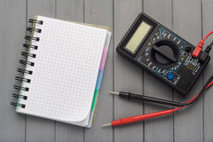 Multimeter on a wooden background next to an empty notepad. Empt. Y space Stock Photo