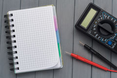 Multimeter on a wooden background next to an empty notepad. Empt. Y space Royalty Free Stock Photography