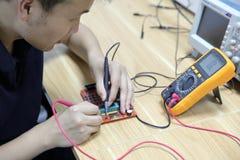 Multimetersonder som undersöker ett datorströmkretsbräde fotografering för bildbyråer