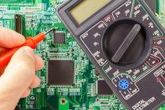 Multimetro di Digital e mano del ` s dell'ingegnere con la sonda sui precedenti del circuito fotografia stock libera da diritti