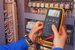 Multimetro nelle mani di un primo piano dell'elettricista su un fondo vago degli elementi elettrici Immagini Stock Libere da Diritti