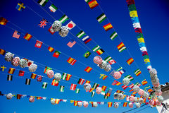 Multinational bunting at a celebration. Multi-national bunting on wires in blue sky Royalty Free Stock Image
