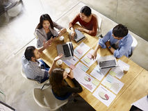 Multinational business team meeting in office. High angle view of a team of asian and caucasian corporate executives discussing business in meeting room royalty free stock photography