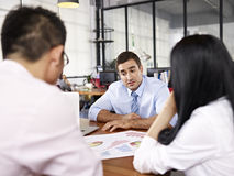 Multinational businesspeople discussing sales performance in off. Two asian business executives discussing business performance with caucasian superior in office Stock Image