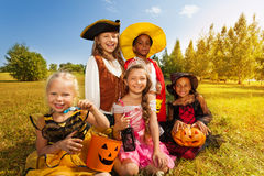 Multinational children in Halloween costumes. Sitting together on the grass with pumpkin and look happily royalty free stock photography