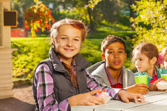 Multinational children sit together at table Royalty Free Stock Images