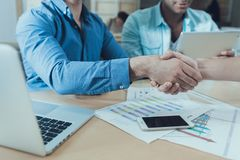 Multinational company of young people makes a deal, confirming it with handshake. Collaboration. stock photography