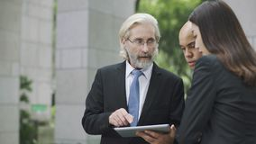 Corporate executives discussing business using digital tablet. Multinational corporate executives discussing business using digital tablet stock image