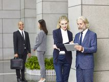 Multinational corporate people standing talking in lobby of mode. Rn office building Stock Image