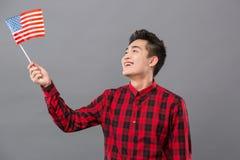 Joyful positive man looking at the US flag. Multinational country. Joyful positive man smiling while looking at the US flag Royalty Free Stock Image