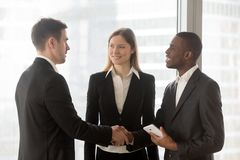 Multinational entrepreneurs handshaking in office. African american and caucasian business partners shaking hands after successful negotiation in office. Young Royalty Free Stock Photos
