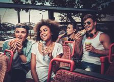 Multinational friends riding on a sightseeing bus Stock Image